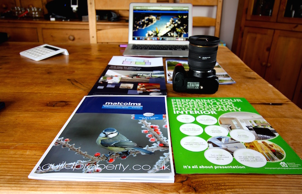 Property marketing material: magazines, camera, laptop