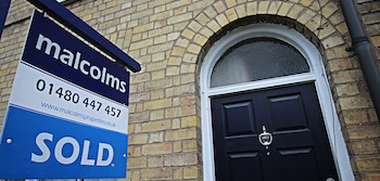 Malcolms sold board outside a house with a black door