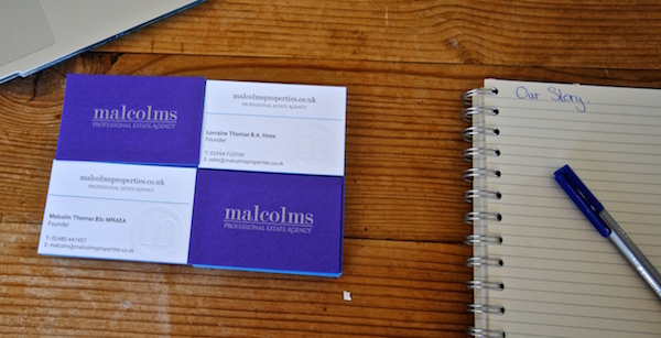 Malcolms Estate Agency's business cards next to notepad and pad