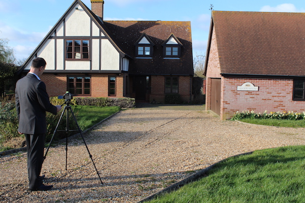 Camera on a tripod with man taking photo of a house