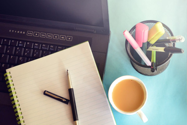 Cup of tea, pot of pens, notepad and laptop