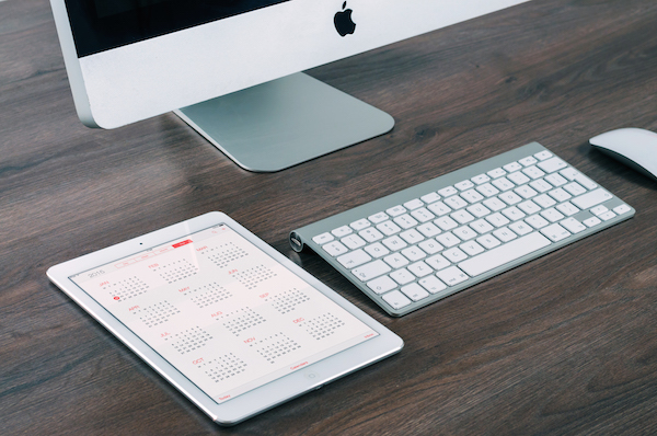 Computer keyboard and iPad with calendar showing