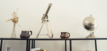 picture of a telescope, vase, globe and jugs on a table