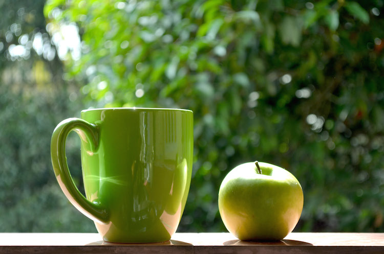 Green mug and apple